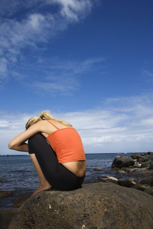 Femme bouleversé s'asseyant sur le rivage rocheux. image libre de droits