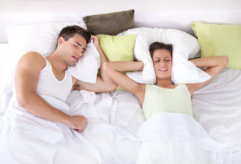 Femme bouleversée dans le lit avec son ami ronflant images stock