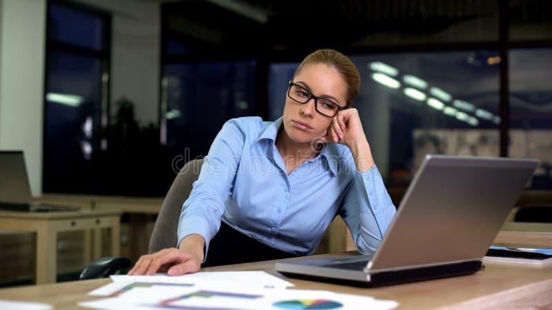 Femme bouleversée et fatiguée d'affaires s'asseyant au bureau tard la nuit, problèmes au travail photo stock