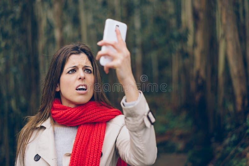 Femme bouleversée regardant le smartphone image libre de droits