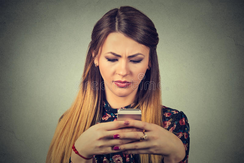 Femme bouleversée tenant le téléphone portable Service de mini-messages de regard triste de fille sur le smartphone photos stock