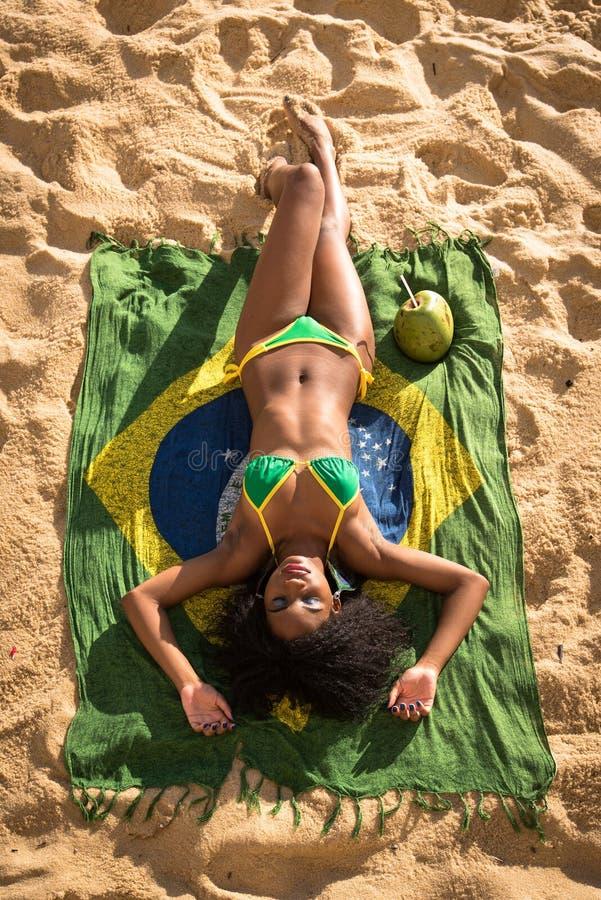 Femme brésilienne dans le bikini détendant à la plage image libre de droits