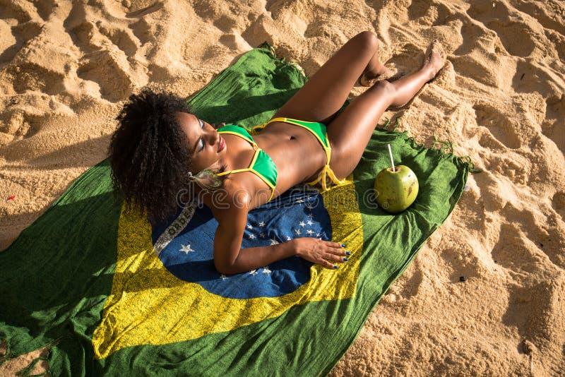 Femme brésilienne dans le bikini détendant à la plage photos libres de droits