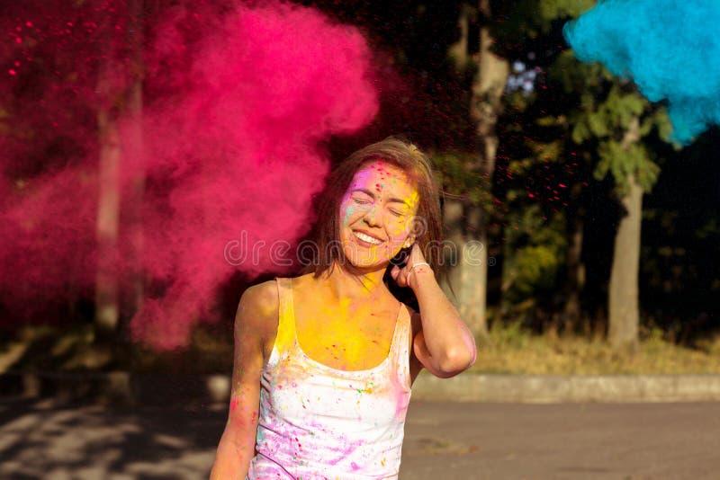 Femme bronzée riante avec les cheveux courts posant avec éclater Holi photo libre de droits