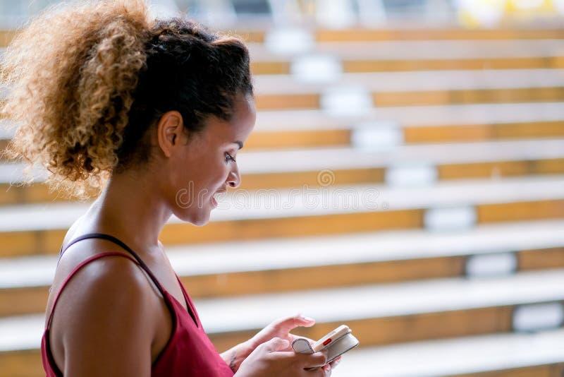 Femme bronzage foncée de métis de peau tenir son téléphone portable et tenir également la manière de promenade du train de ciel p images stock