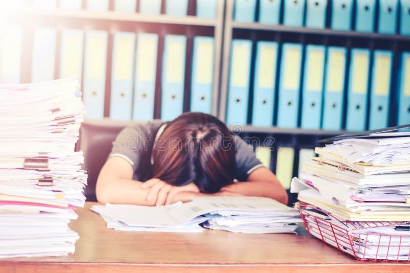 Femme brouillée d'affaires endormie sur le bureau au bureau avec des documents de pile d'écritures de f et le concept de feuille  photos stock