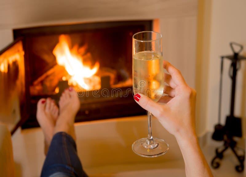 Femme buvant Champagne devant un feu image stock