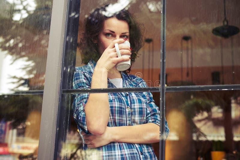Femme buvant du café et examinant la distance photo stock