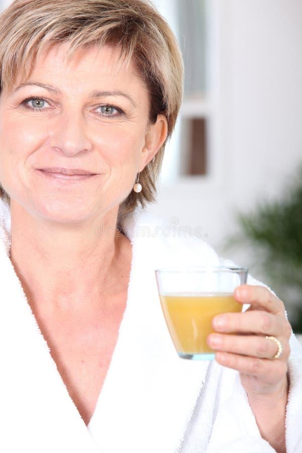 Femme buvant du jus d'orange photographie stock