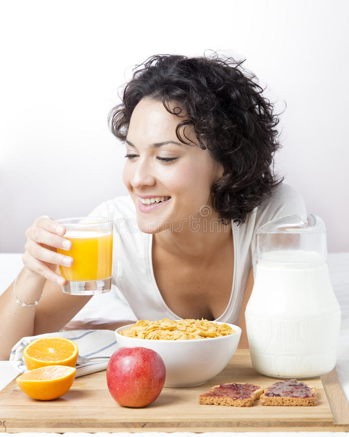 Femme buvant du jus d'orange frais pour le petit déjeuner sain sur le blanc photographie stock libre de droits