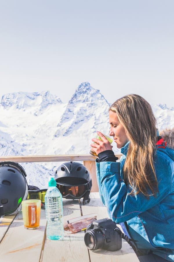 Femme buvant du thé chaud dans le sommet extérieur en bois rustique de montagne de café Concept de touristes d'aventure de mode d photographie stock
