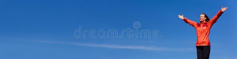 Femme célébrant des bras augmentés dans le panorama de ciel bleu image stock