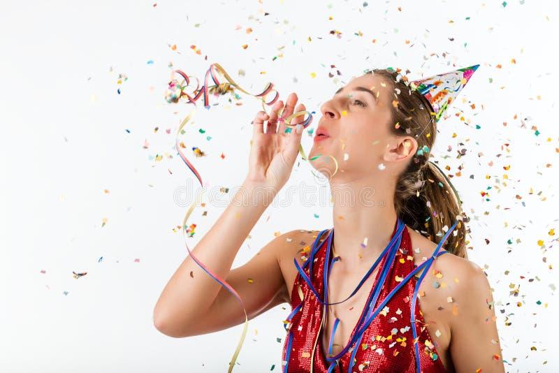 Femme célébrant l'anniversaire avec le chapeau de flamme et de réception photographie stock libre de droits