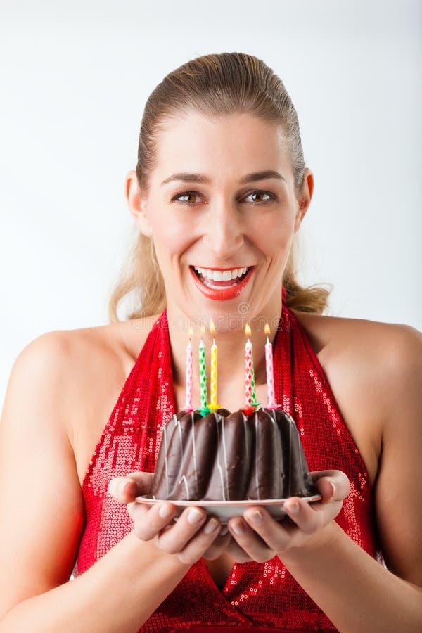 Femme célébrant l'anniversaire avec le gâteau et les bougies photos stock