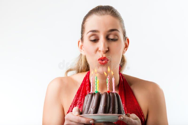 Femme célébrant l'anniversaire avec le gâteau et les bougies image libre de droits