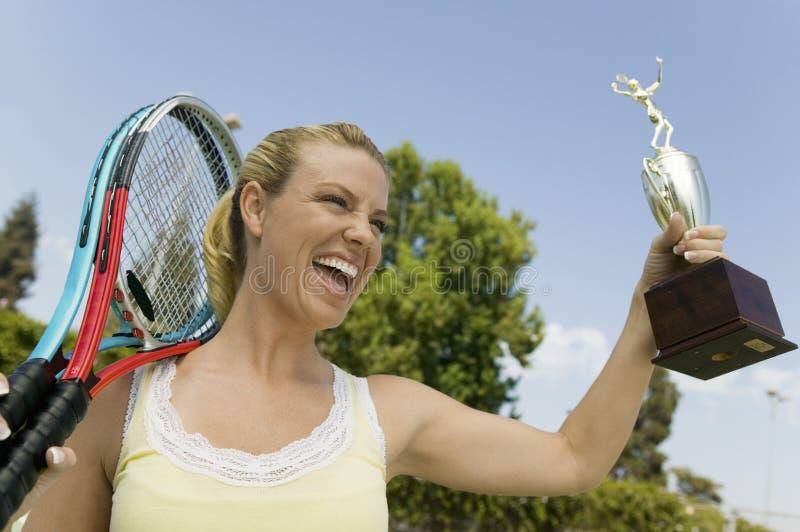 Femme célébrant sur le court de tennis avec les raquettes et le trophée de tennis photos stock