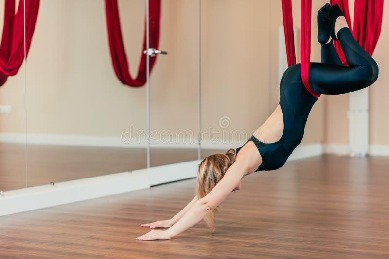 Femme célibataire de yogi faisant la pratique en matière aérienne de yoga dans l'hamac pourpre dans le centre de fitness photo libre de droits