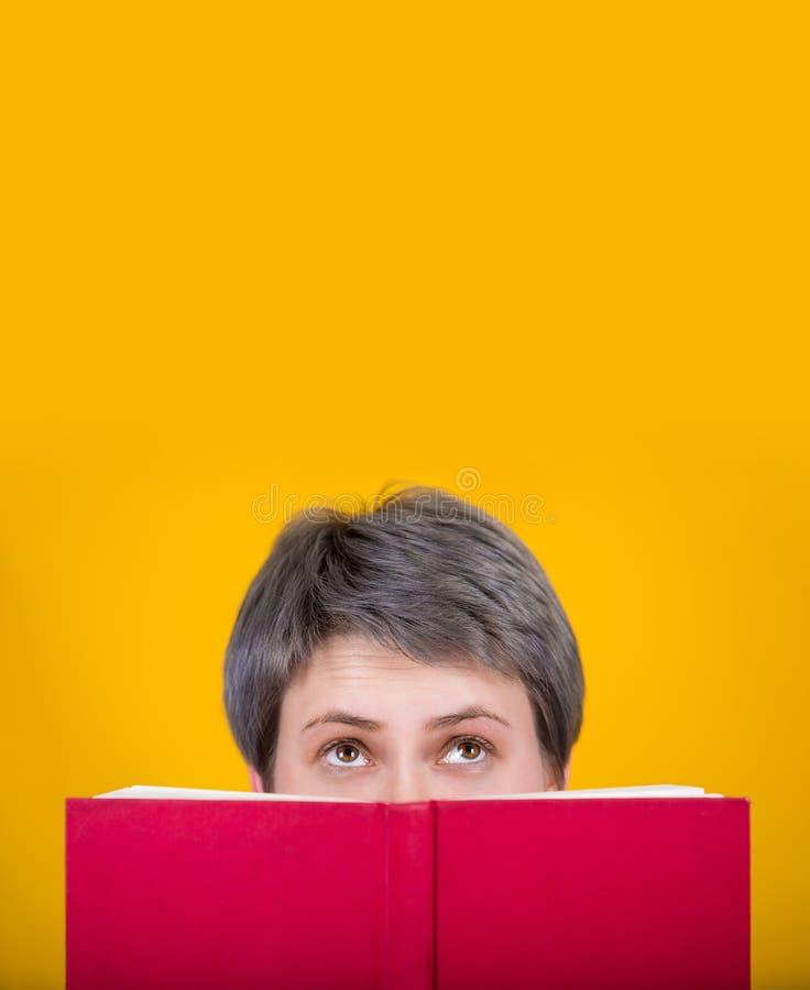 Femme cachée derrière le livre image libre de droits