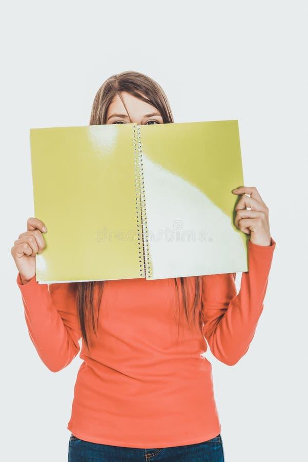 Femme cachant son visage derrière un carnet photographie stock