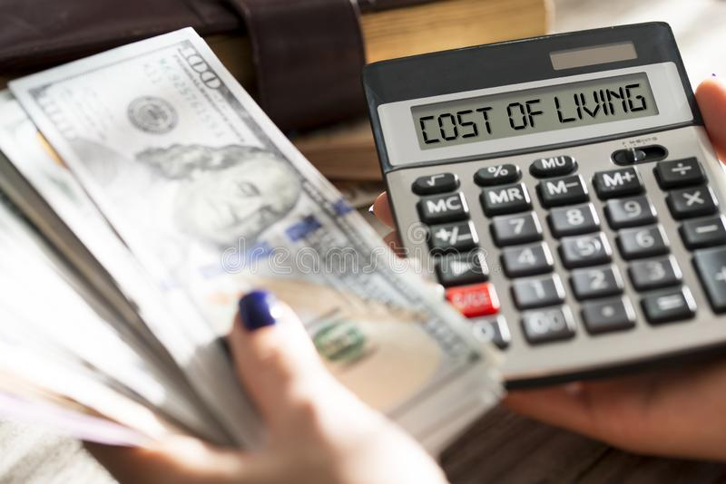 Femme calculant le coût de la vie avec l'argent liquide de calculatrice billets de banque de dollar US photographie stock