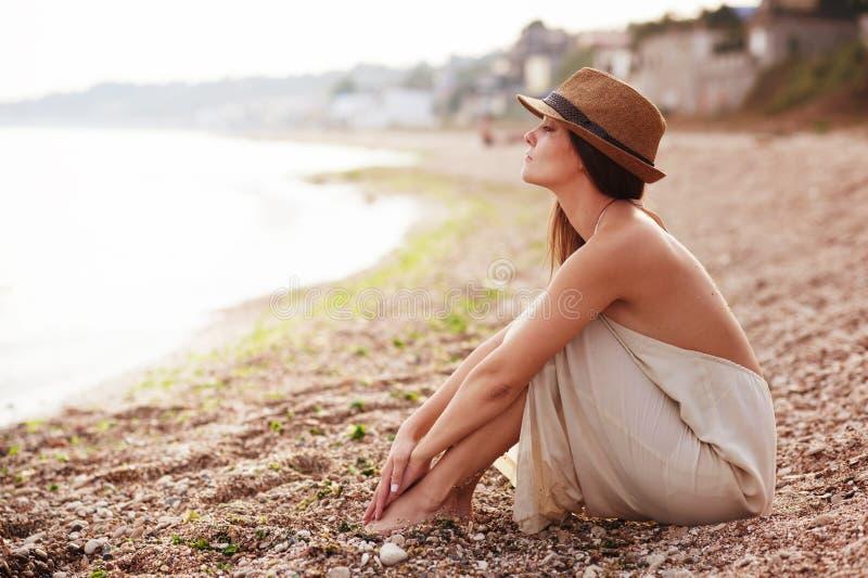 Femme calme seul s'asseyant sur une plage de sable photographie stock