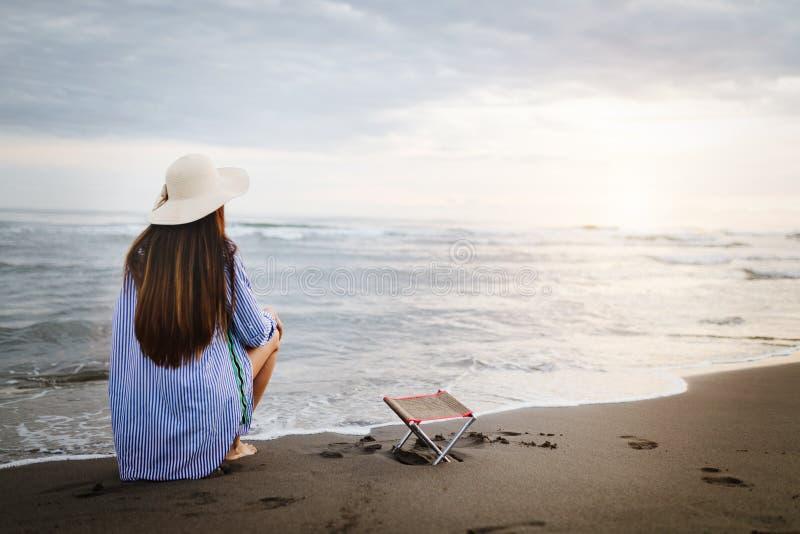 Femme calme seul s'asseyant sur une plage de soir?e de sable photo stock