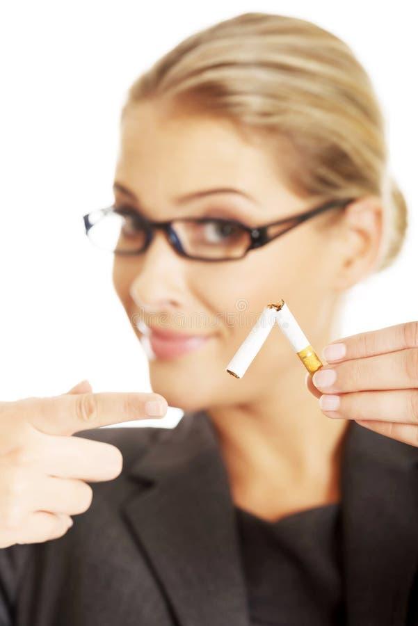 Femme cassant la cigarette pour cesser tabagisme image libre de droits
