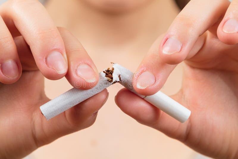 Femme cassant une cigarette images stock