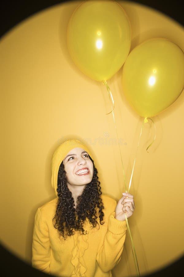 Femme caucasien avec des ballons utilisant l'imperméable jaune. photos stock