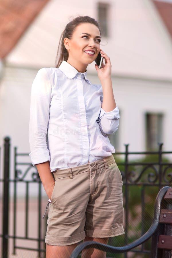 Femme caucasienne assez de sourire de brune parlant du téléphone portable Pose dehors photos libres de droits