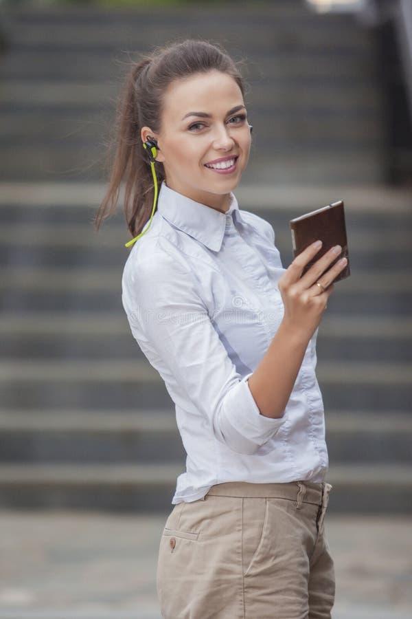 Femme caucasienne assez de sourire de brune avec des écouteurs et causerie sur le téléphone portable photos stock