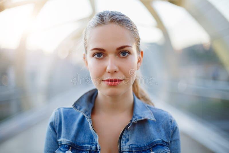 femme caucasienne blanche de sourire de fille avec la queue de poney, veste de port de jeans dehors dans le pont en rue de ville  photos stock