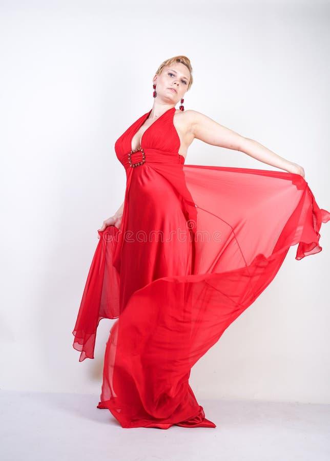 Femme caucasienne blonde chaude portant la longue robe égalisante rouge et posant sur seul le fond blanc de studio fille adulte à photo libre de droits