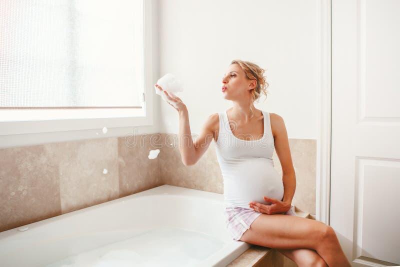 Femme caucasienne blonde enceinte dans la salle de bains pendant le matin photos libres de droits