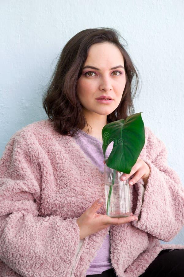 femme caucasienne calme dans le manteau de fourrure fascinant posant dans le studio avec la feuille tropicale de monstera vert, m photo stock