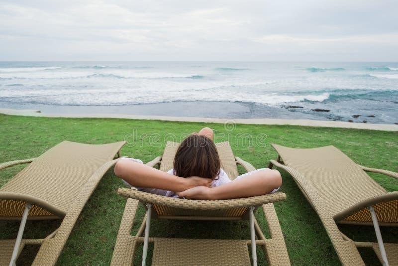Femme caucasienne détendant dans la chaise près de l'Océan Indien au Sri Lanka image stock