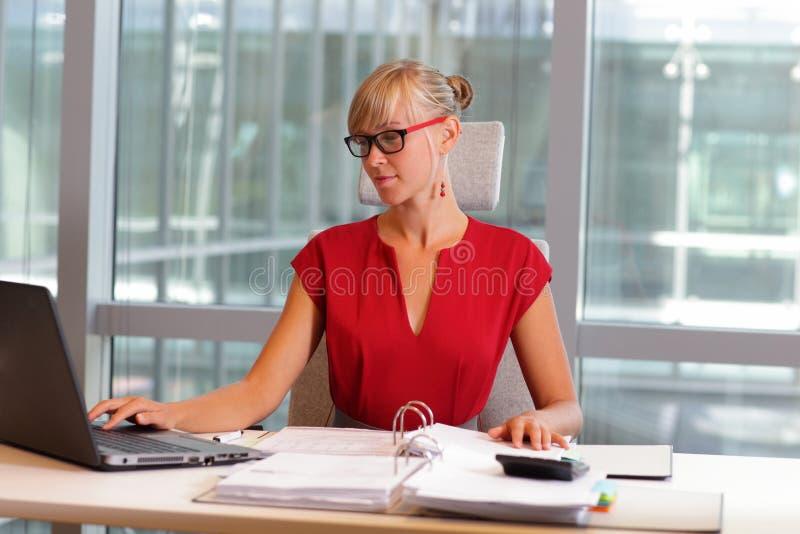 Femme caucasienne d'affaires dans des lunettes travaillant sur l'ordinateur portable image stock
