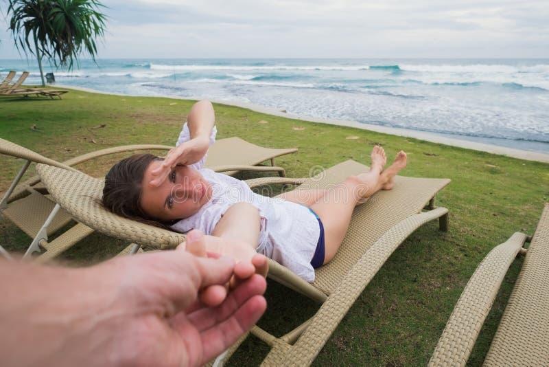 Femme caucasienne dans la chaise près de la plage tenant sa main de mari Suivez-moi concept photo libre de droits