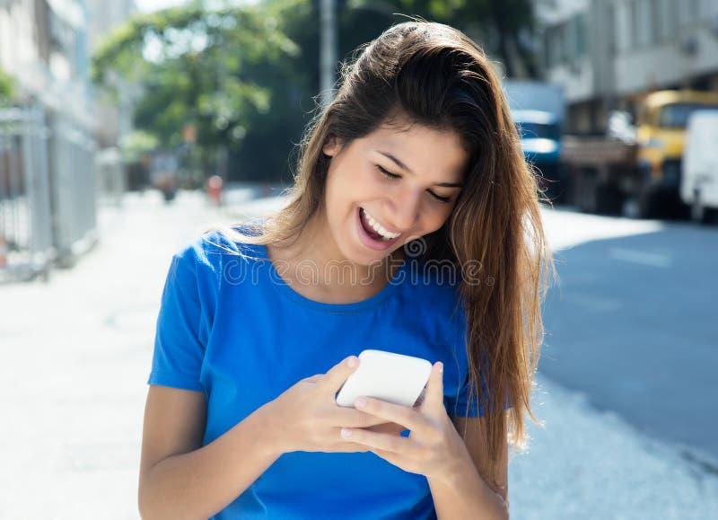 Femme caucasienne dans la chemise bleue surfant le Web avec le téléphone image libre de droits