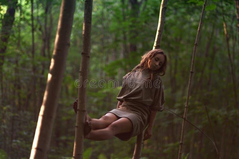 Femme caucasienne dans la robe se reposant entre les arbres dans la forêt photos stock