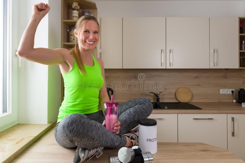 Femme caucasienne dans le costume de gymnase avec la boisson de protéine dans la pose de victoire photographie stock