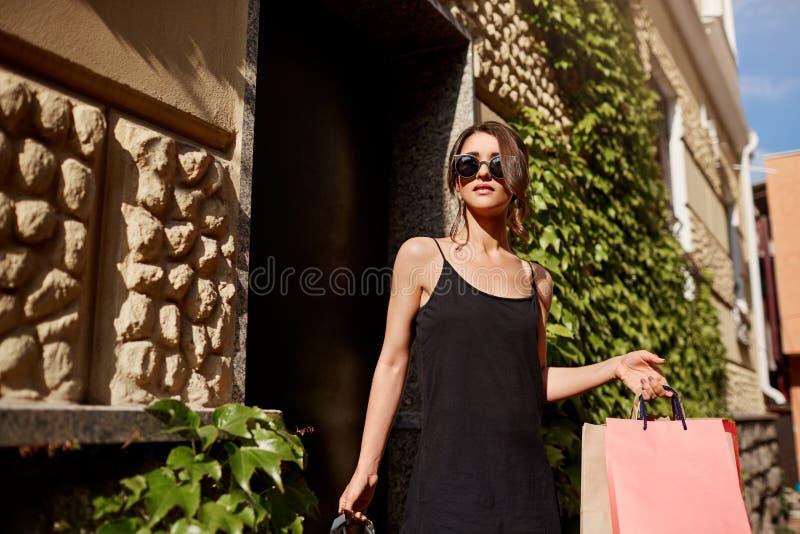 Femme caucasienne de jeune brune belle à la mode dans les lunettes de soleil et la robe noire quittant le magasin avec des panier photographie stock