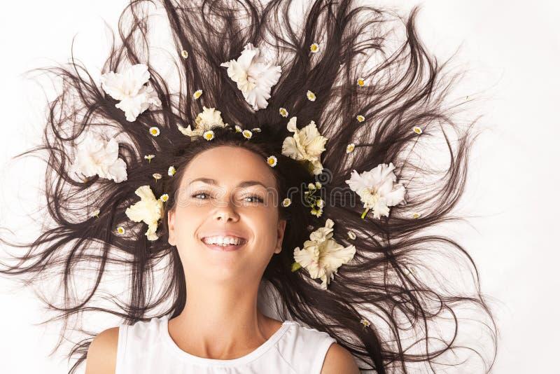 Femme caucasienne de sourire de brune s'?tendant sur le plancher avec des cheveux ?cart?s photographie stock