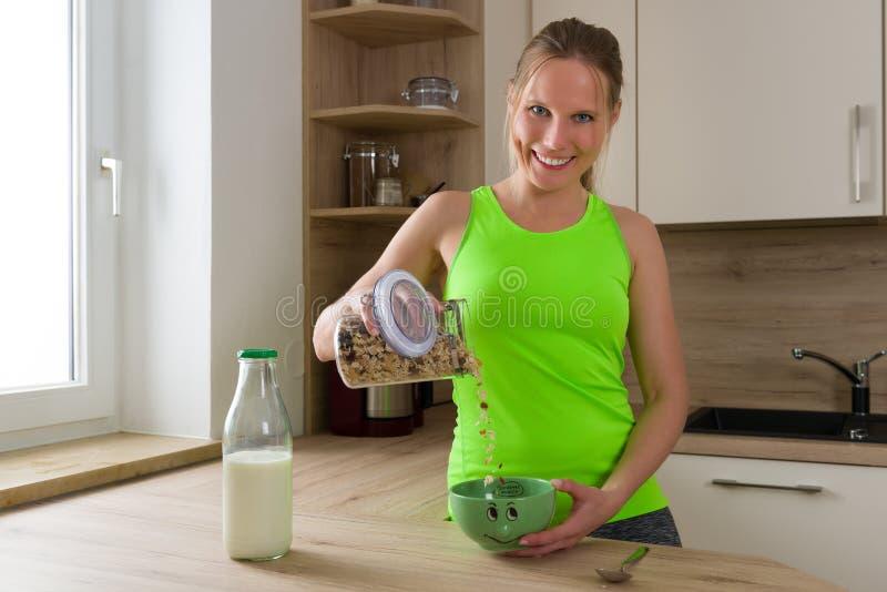 Femme caucasienne en céréales de mélange de costume de gymnase (muesli) avec du lait image stock