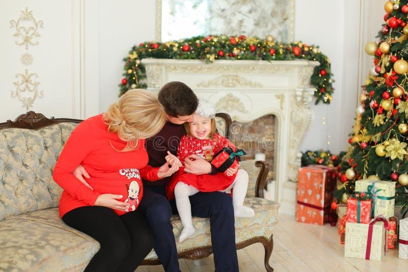Femme caucasienne enceinte s'asseyant avec l'homme et la fille près de l'arbre de Noël et de la cheminée décorée photo libre de droits