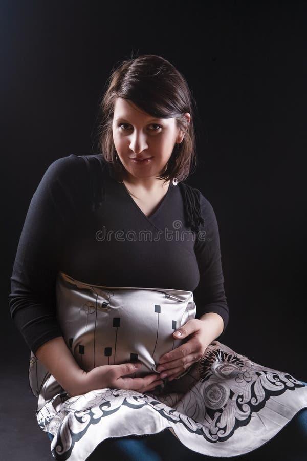 Femme caucasienne enceinte tranquille dans la robe de soutien Se reposer sur le fond noir photographie stock libre de droits
