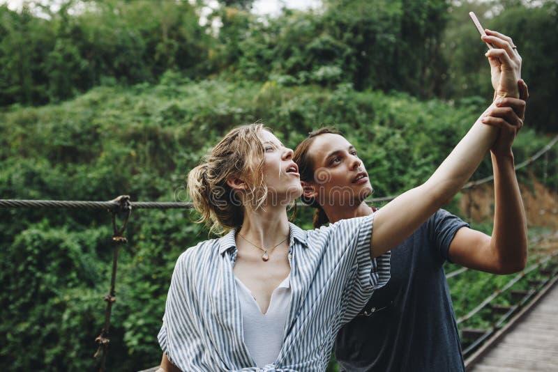 Femme caucasienne et homme prenant un selfie dehors image stock