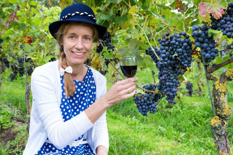 Femme caucasienne grillant avec le verre de vin près des groupes de bleu photographie stock