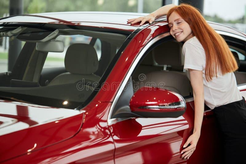 Femme caucasienne heureuse embrassant sa nouvelle voiture au concessionaire automobile images libres de droits