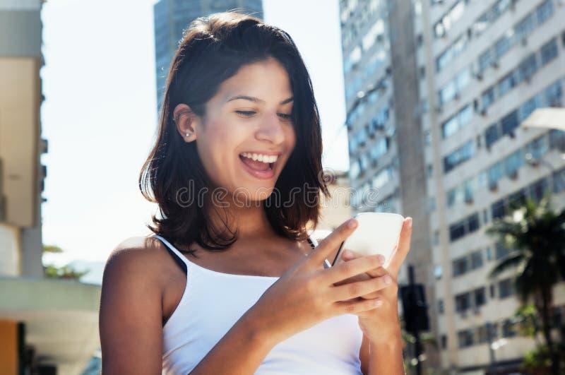Femme caucasienne heureuse surfant l'Internet avec le téléphone image libre de droits